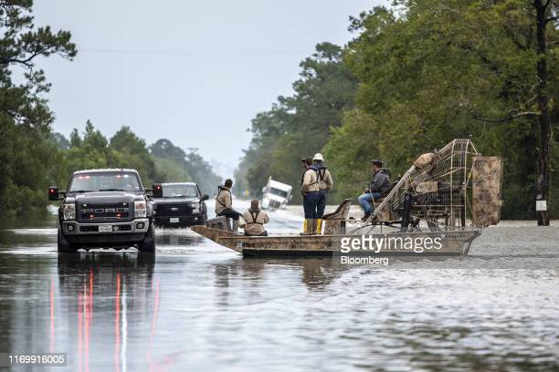 Volunteers travel in a boat along a flooded highway following Tropical Storm Imelda in Fannett Texas US on Friday Sept 20 2019 The remnants of...