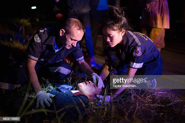 Volunteers treat a severely injured motorbike accident victim on the side of the road on December 6 2014 in Vientiane Laos Vientiane Rescue is an...