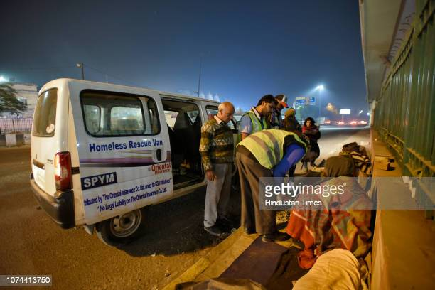 Volunteers try to convince homeless people sitting on a pavement of a road at Nizamuddin Basti on December 18 2018 in New Delhi India There are some...