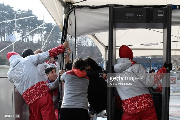 Volunteers try to stop a security control tent from flying away by strong winds outside the Gangneung Ice Arena in Gangneung during the Pyeongchang...
