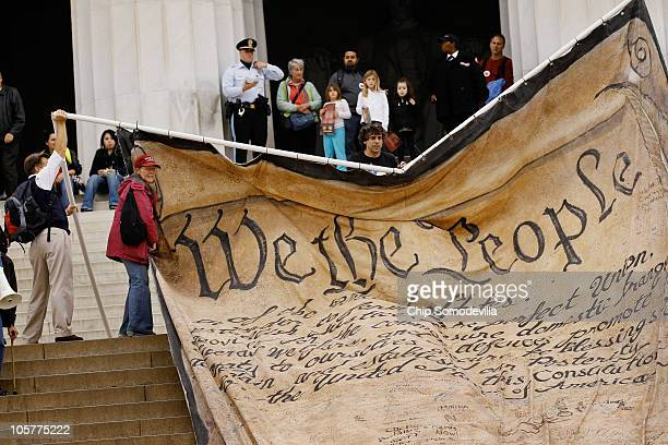 Volunteers unfurl a giant banner printed with the Preamble to the United States Constitution during a demonstration against the Supreme Court's...