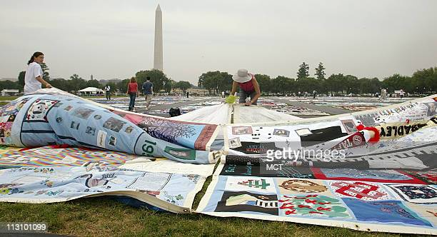 Volunteers unfurl panels of the AIDS Memorial Quilt on the Ellipse in Washington DC as names of those who died from AIDS are read aloud on Friday...