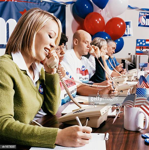 volunteers using telephones in a political campaign office - political rally stock pictures, royalty-free photos & images