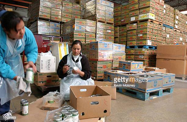 Volunteers Veronica Rodriguez and Virginia Flores process donated food at the Food Bank of the Rockies January 29 2003 in Denver Colorado The Food...