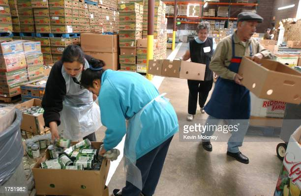 Volunteers Virginia Flores and Veronica Rodriguez sort donated food while Shirley Perry and Bacilio Sosa move boxes at the Food Bank of the Rockies...