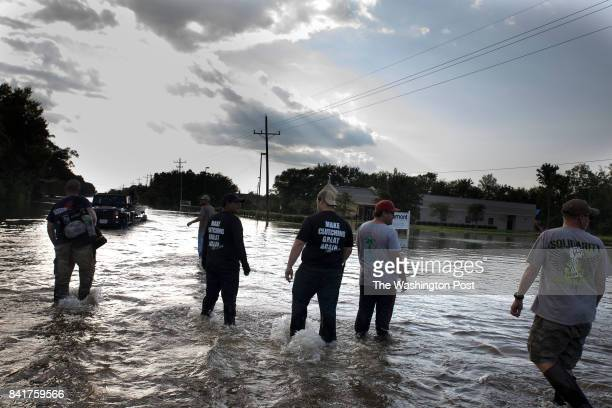 Volunteers wait for a boat to be dismounted from a truck so that they can search a flooded section of Beaumont for survivors Most people they found...