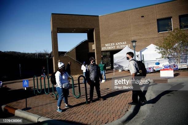 Volunteers wait for students to arrive to vote at a polling place located next to a COVID19 testing center on the campus of Appalachian State...