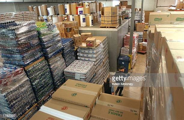 Volunteers walk among stacks of donated food at the Food Bank of the Rockies January 29 2003 in Denver Colorado The Food Bank of the Rockies is a...
