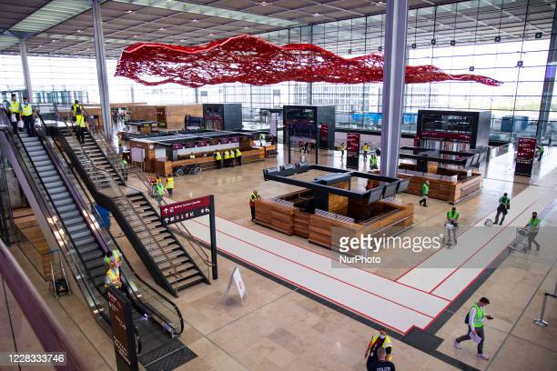 Volunteers walk inside the check-in hall at Berlin Brandenburg Airport 'Willy Brandt' during a test run ahead of its opening, planned for October 31,...