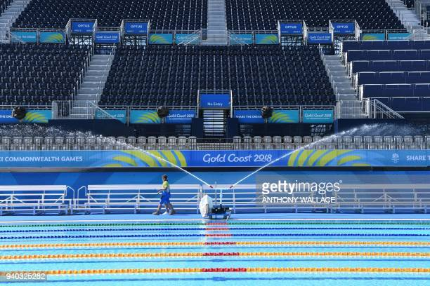 Volunteers walk past pumps which are used to cool the swimming pool water at the Optus Aquatic Centre ahead of the 2018 Gold Coast Commonwealth Games...