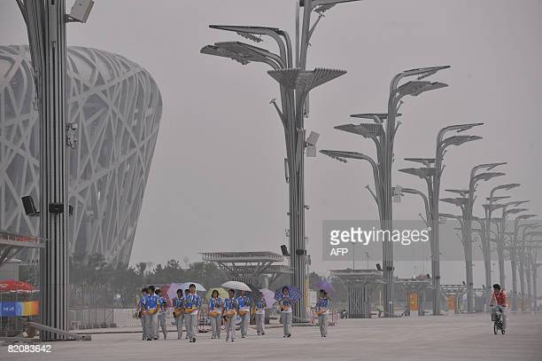 Volunteers walk through the smog on the Olympic Green in Beijing on July 28, 2008. With just 11 days to go before the start of the world's biggest...