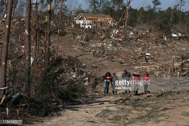 Volunteers walk with local residents who were affected after the area was destroyed by a tornado touchdown March 6 2019 in Beauregard Alabama...