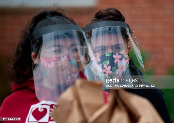 Volunteers wear faces shields as they wait to hand out meals and groceries to families during a COVID19 community support program sponsored Maryland...