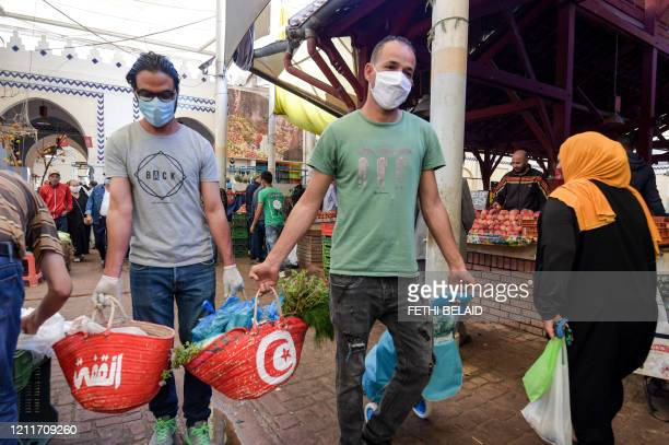 Volunteers wearing face masks due to the COVID-19 coronavirus pandemic distribute food aid at the central market in the Tunisian capital Tunis on May...
