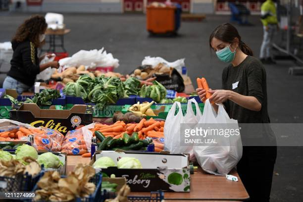 Volunteers wearing PPE of a face mask as a precautionary measure against COVID-19, work to sort food and create food parcels, for those in need due...