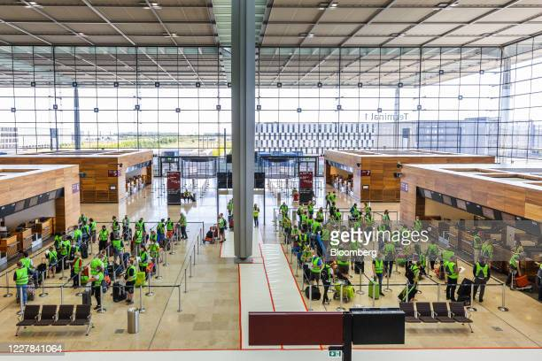 Volunteers wearing protective face masks queue with luggage during a passenger check-in test run demonstration at Berlin Brandenburg Airport ,...
