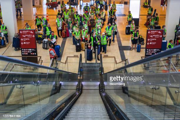 Volunteers wearing protective face masks wait to board an escalator during a test run at Berlin Brandenburg Airport , operated by Flughafen Berlin...