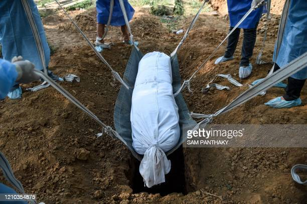 Volunteers wearing protective gear lower a dummy dead body lying on a stretcher with straps, to be used for coronavirus victims, in a burial pit...