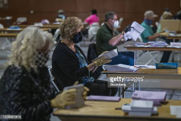 Volunteers wearing protective masks and gloves sort through early voting ballots in Martinez, California, U.S., on Wednesday, Oct. 28, 2020. With six...
