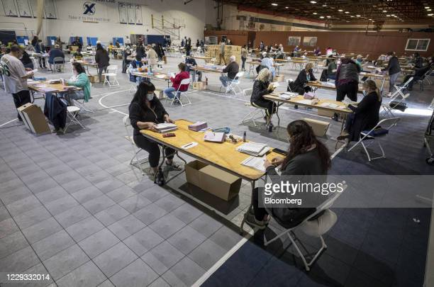 Volunteers wearing protective masks sort through early voting ballots in Martinez, California, U.S., on Wednesday, Oct. 28, 2020. With six days until...