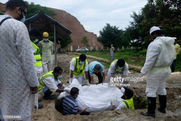 Volunteers wearing protective suits carry the body of a Coronavirus victim for burial. Bangladesh has recorded a total of 130,474 confirmed cases, of...