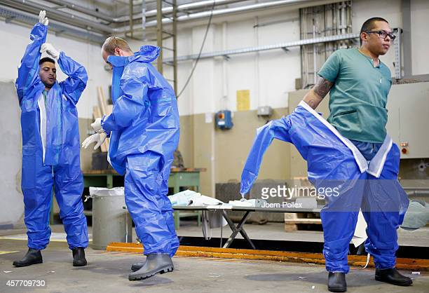 Volunteers who responded to a nationwide appeal by the German Red Cross to help in the fight against ebola in Africa put on isolation suits during...