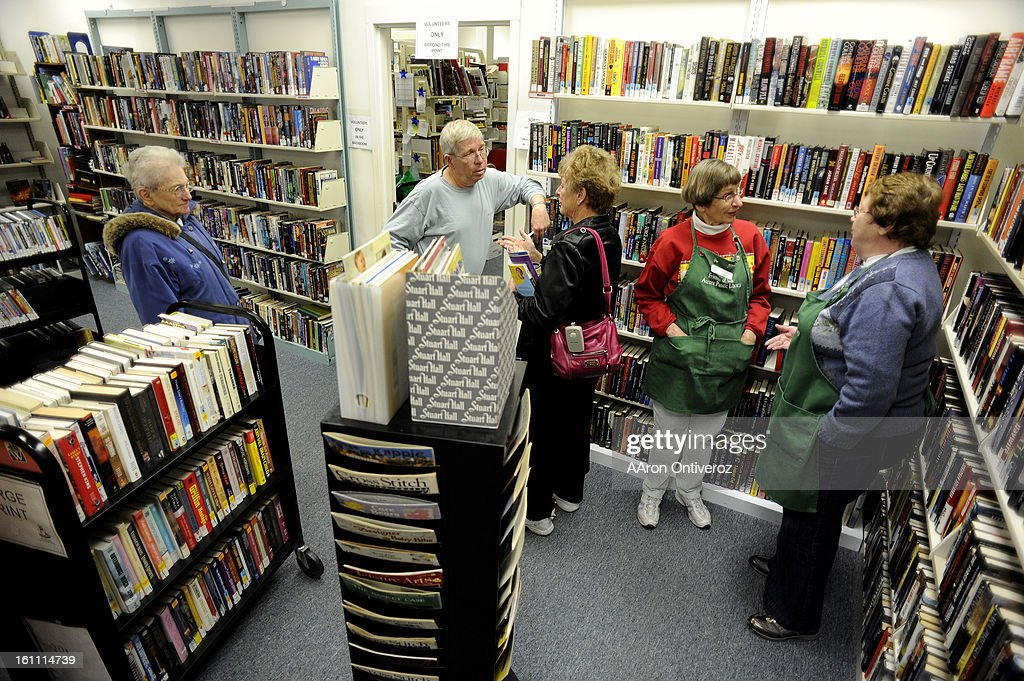Volunteers who work at the Friends of the Aurora Library Book Store chat amongst one another at the store. The store, which has been in operation for more than 30 years, sells used books and donates proceeds to the Aurora public libraries' collections --  : News Photo
