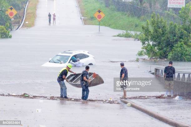 Volunteers with a canoe makes their way to assist a driver that was stalled going through high water during Hurricane Harvey Monday August 29 2017