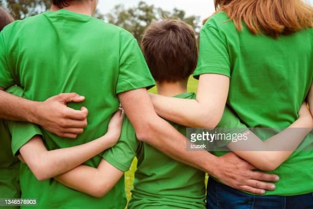 volunteers with arms around in park - izusek stock pictures, royalty-free photos & images
