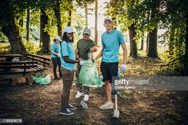 volunteers with garbage bags cleaning in public park - campaigner stock pictures, royalty-free photos & images