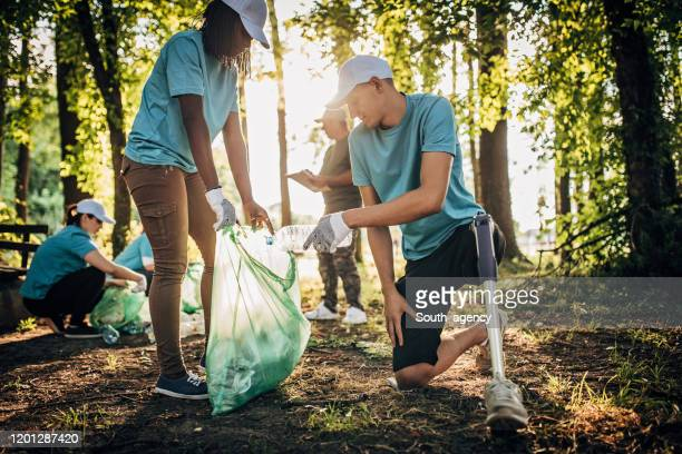 volunteers with garbage bags cleaning park area - disability collection stock pictures, royalty-free photos & images