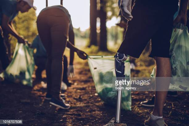 volunteers with garbage bags cleaning park - disability collection stock pictures, royalty-free photos & images