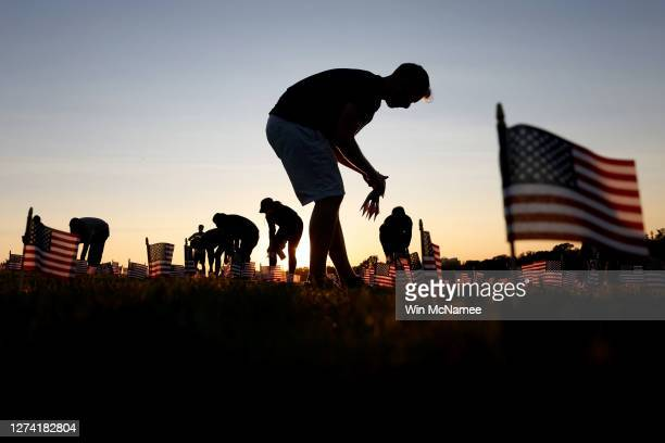 Volunteers with the COVID Memorial Project install 20,000 American flags on the National Mall as the United States crosses the 200,000 lives lost in...