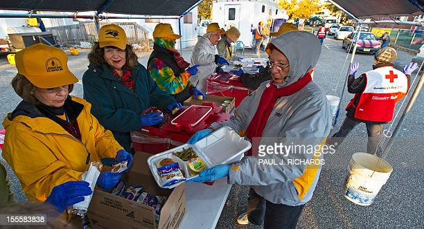 Volunteers with the North Carolina Baptist Men's Disaster Relief work with volunteers from the American Red Cross preparing hot meals on an assembly...
