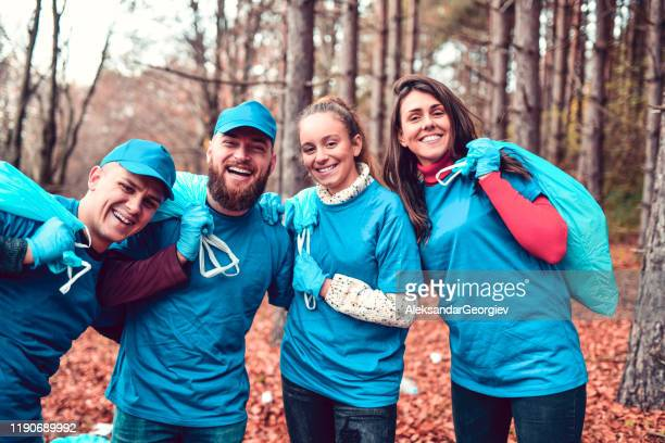 volunteers with their bags of collected garbage from park - social responsibility stock pictures, royalty-free photos & images