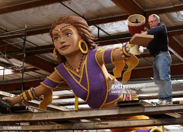 Volunteers work on floats to be included in the annual Tournament of Roses Parade in Pasadena that will take place before the Rose Bowl collegiate...