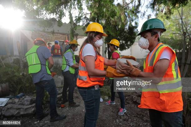 Volunteers work removing debris from a collapsed house four days after the magnitude 71 earthquake jolted central Mexico killing more than 250...
