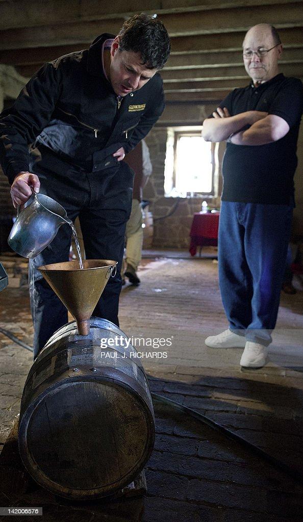Volunteers work the wood fired still boi : News Photo