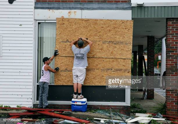 Volunteers work to board up buildings damaged by a tornado on Main Street in Webster MA on Aug 4 2018 A tornado along with intense rain hit Central...