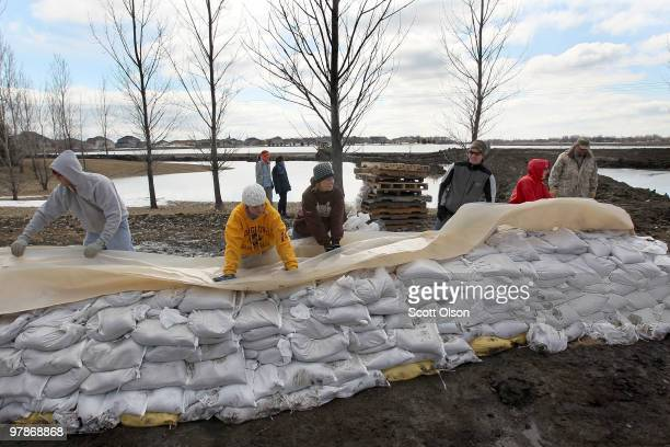 Volunteers work to build a sandbag levee after flood water began to seep through an existing levee near the Timberline subdivision March 19, 2010 in...