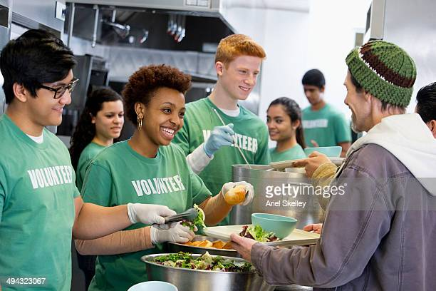 volunteers working in soup kitchen - homeless foto e immagini stock