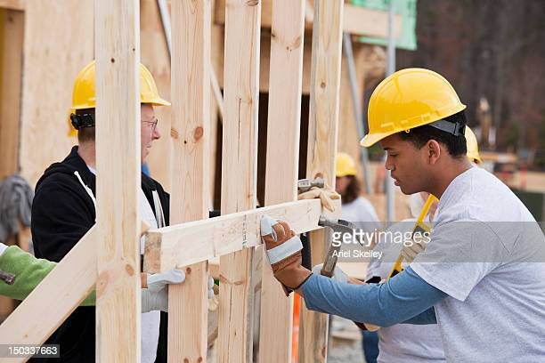 volunteers working on construction site - humanitarian aid stock pictures, royalty-free photos & images