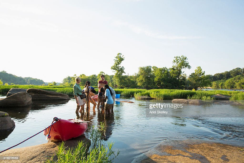 Volunteers working together in river : Stock Photo