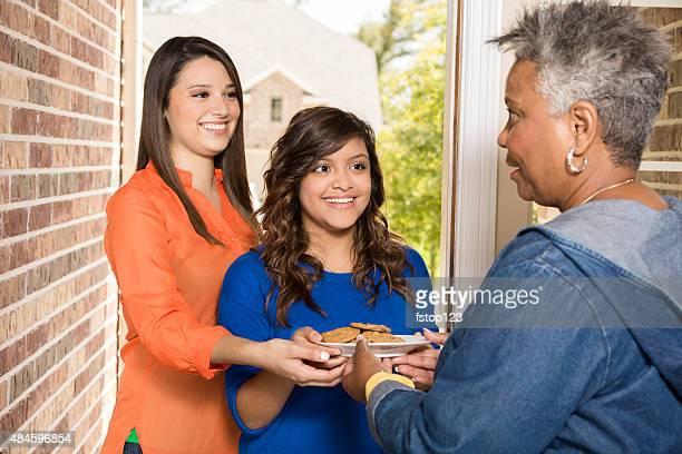 Bénévoles: Jeunes adultes avec des cookies pour femme senior à la maison.