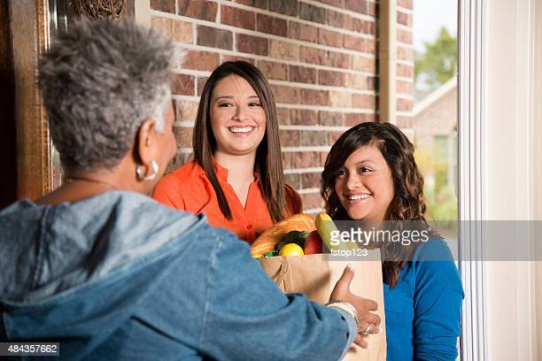 volunteers:  young adults bring groceries to senior woman at home. - meals on wheels stock pictures, royalty-free photos & images