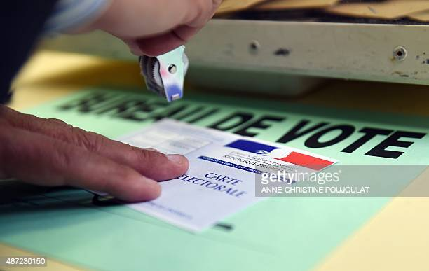 A volunter stamps an electoral card at a polling station during the first round of the French departementales elections on March 22 2015 in Marseille...