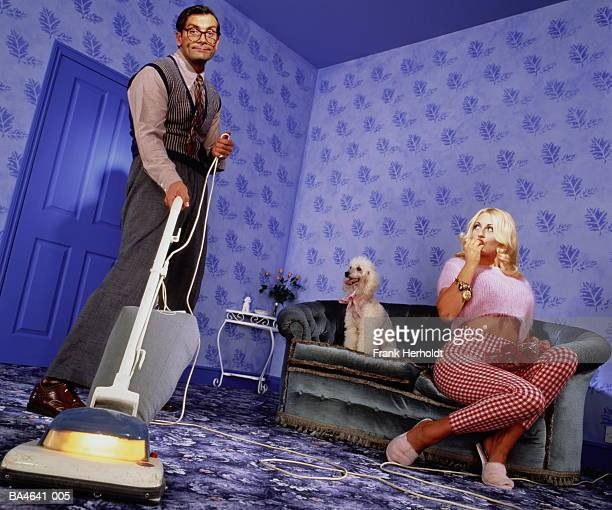 voluptuous woman sitting on sofa eating strawberries, man vacuuming - may december romance stock photos and pictures