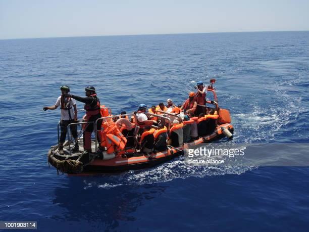 Von einemSchlauchboot im Mittelmeer gerettete Migranten sitzen am auf einemBoot der Hilfsorganisationen Ärzte ohne Grenzen und SOSMediterranee...
