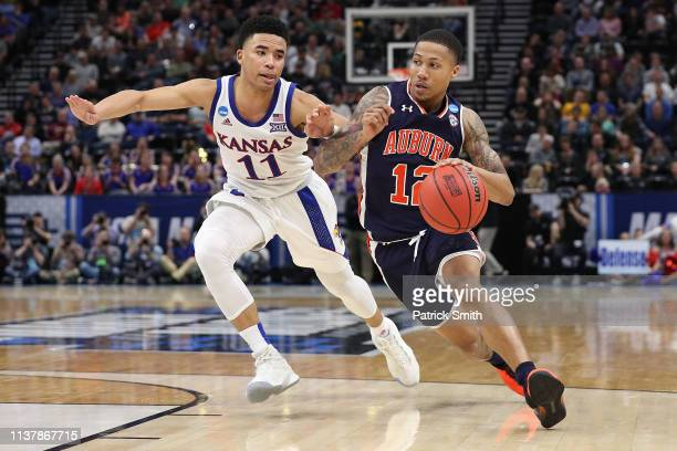 Von McCormick of the Auburn Tigers drives with the ball against Devon Dotson of the Kansas Jayhawks during their game in the Second Round of the NCAA...