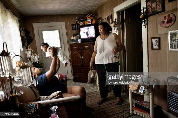 Vonda Wells stands with her Oxygen supply at home with her daughter Brandyce Wells and Brandyce's four month old daughter Imari in Clinton...
